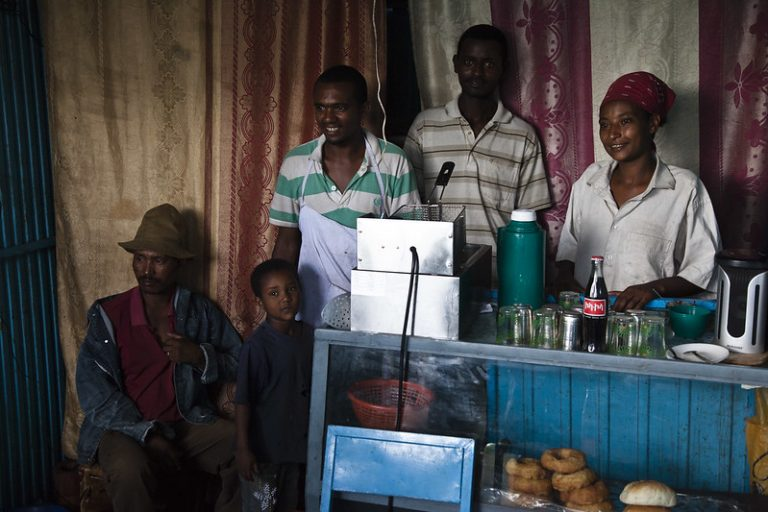 image of Ethiopian people standing behind a counter selling coca-cola and doughnuts