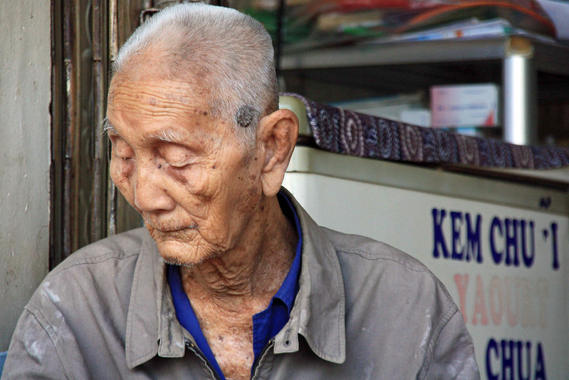 An old Vietnamese man looking down