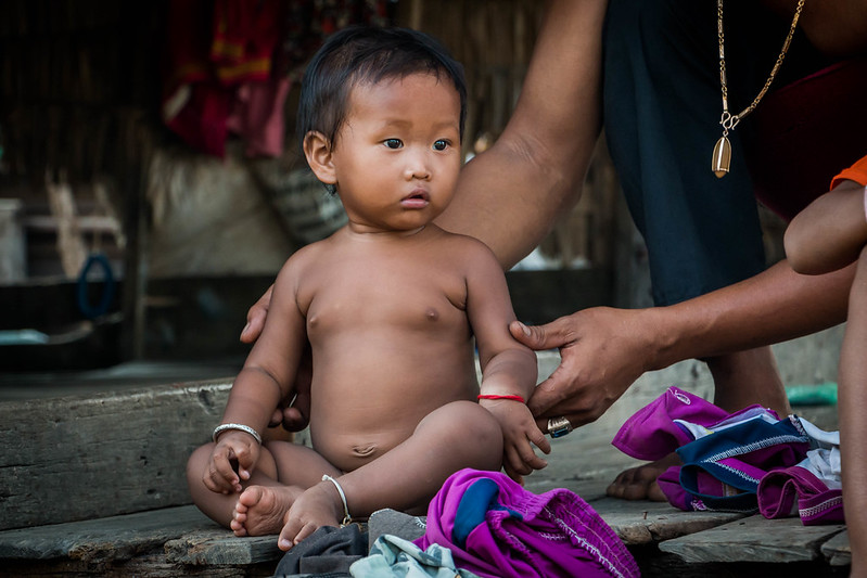 Arms holding sitting Cambodian baby