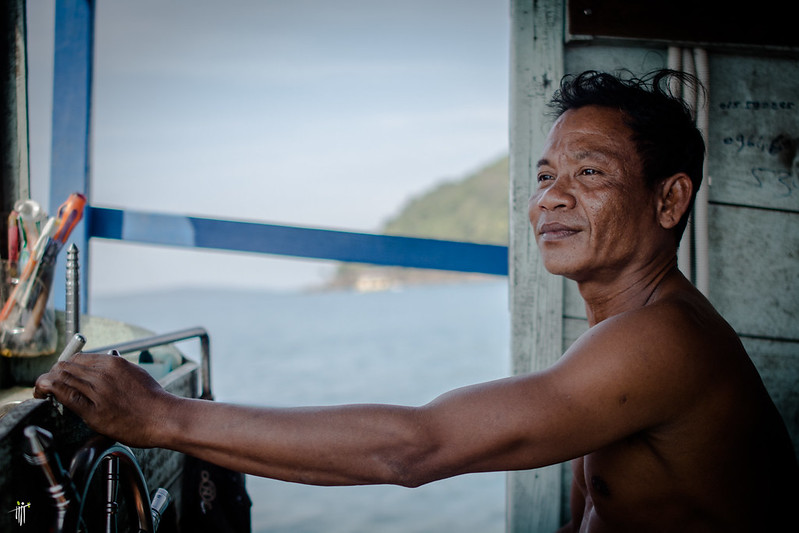 Cambodian man smiling on boat