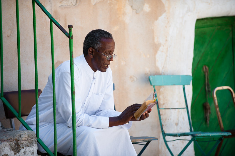 Ethiopian Orthodox priest reading on steps