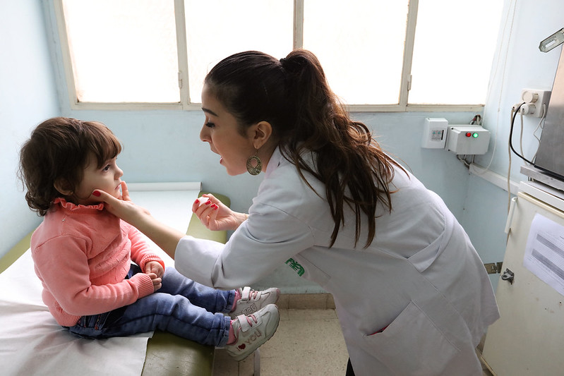 Toddler receiving health care from professional.