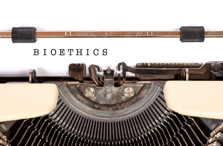 "close up of a typewriting with the word ""bioethics"" typed out on a sheet of white paper"