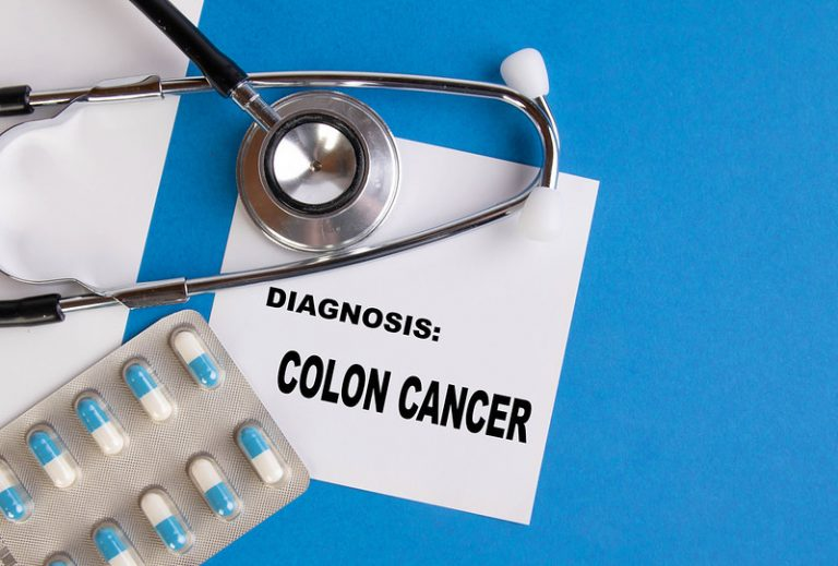 stethoscope and pills over colon cancer diagnosis