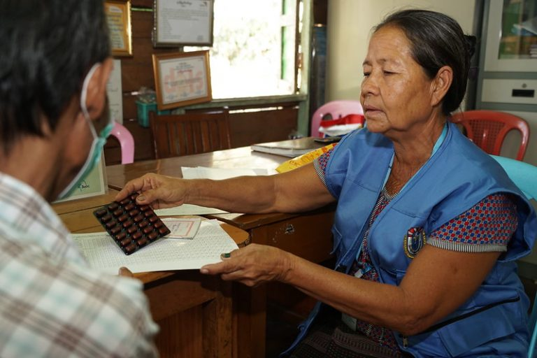 A community health worker giving medicine to a patient