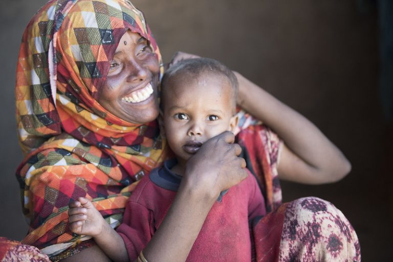 Somali woman smiling and holding child