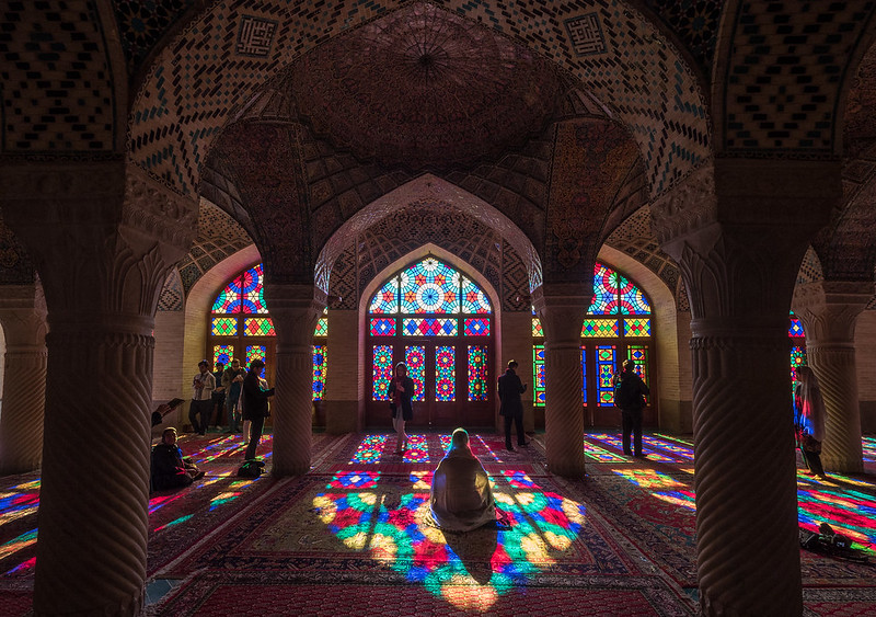 Image of light streaming through stained glass inside of a mosque