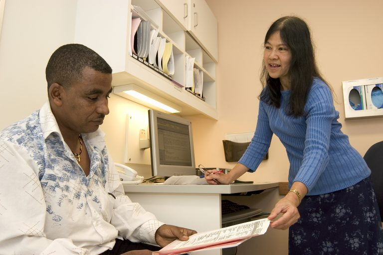Photo of a health care provider going over a form with a patient