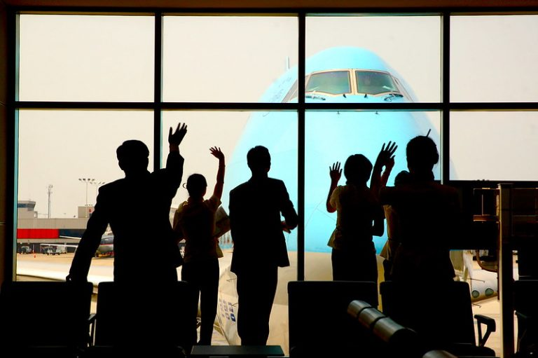 People waving from inside an airport as an airplane taxis