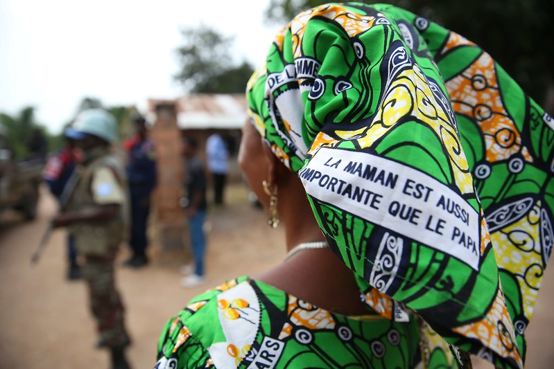 "Photo of the back of a woman's head, wearing African print fabric with French text that translates to: ""The mom is as important as the dad"". Military personnel appear in the background."
