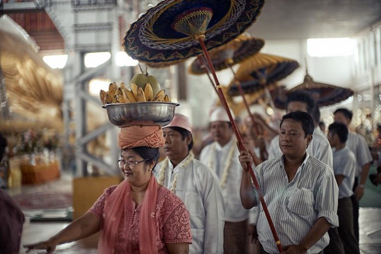Image of Burmese processing lead by a woman carrying bananas on her head
