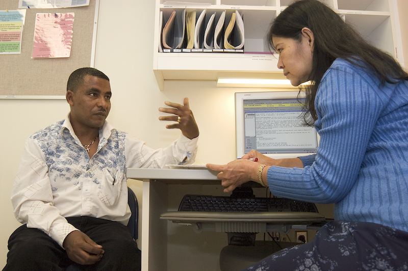 A provider having a discussion with a patient in a clinic exam room