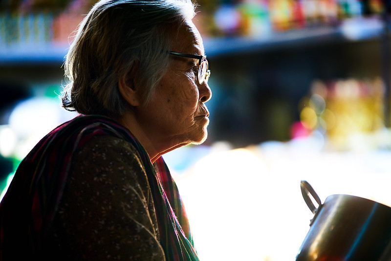 elderly cambodian woman sitting in the marketplace