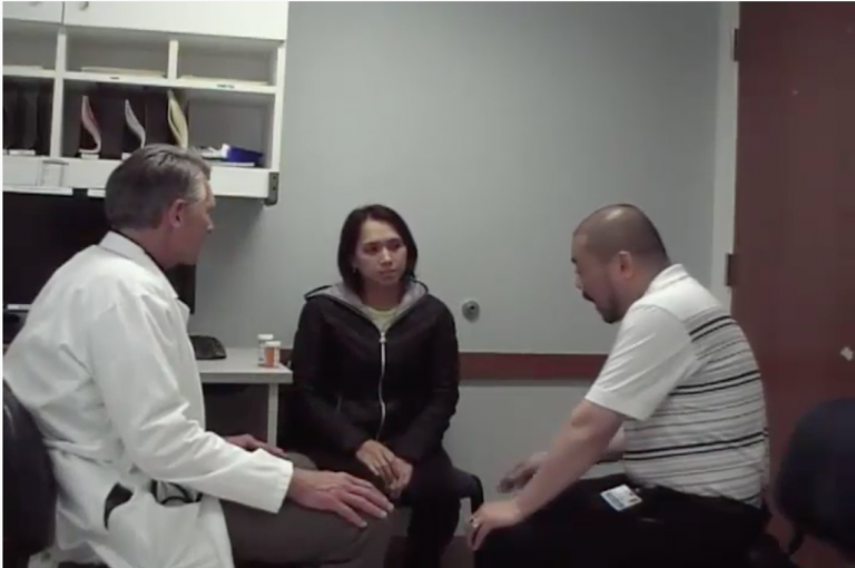 A doctor, patient and medical interpreter in a clinic exam room