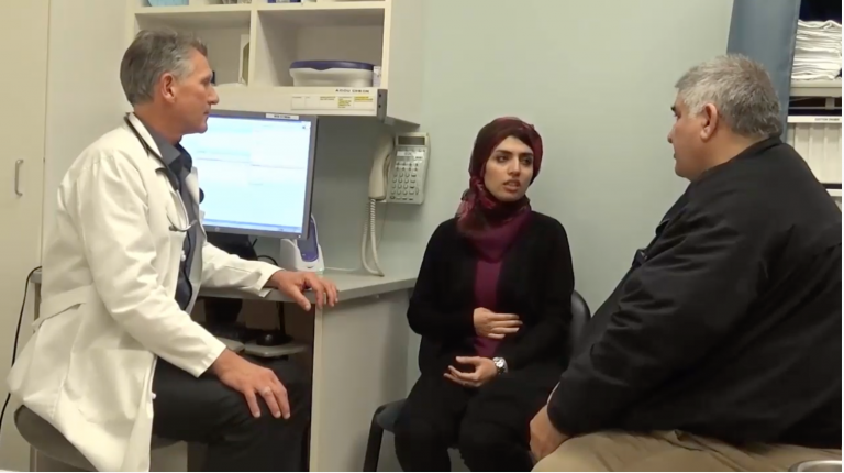 A doctor, a patient and a medical interpreter in a medical exam room