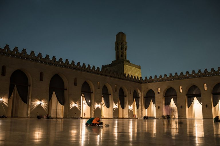 Two muslims praying in the courtyard of a mosque at dusk
