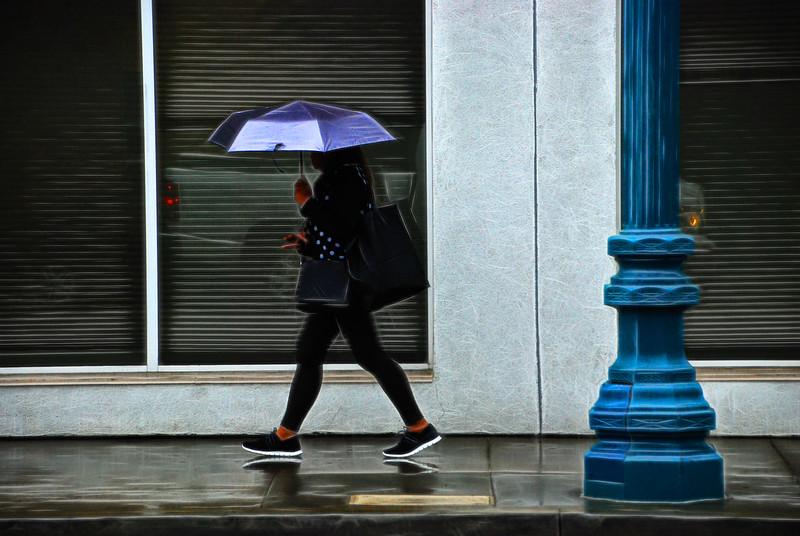 person in rain with a blue umbrella