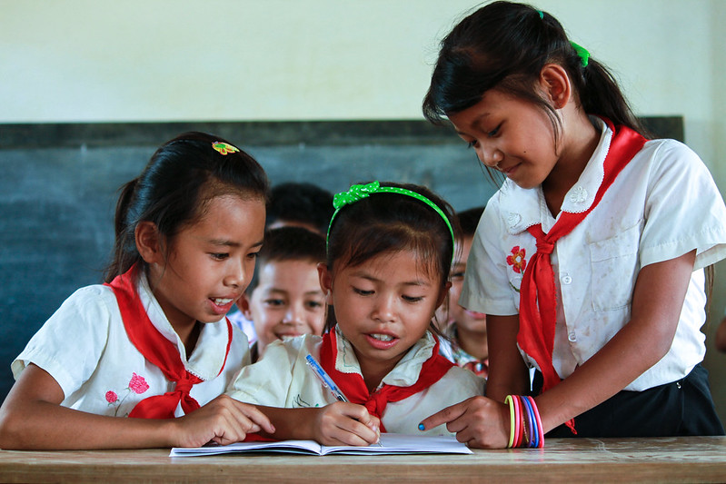 Three school children in a classroom in Southeast Asia