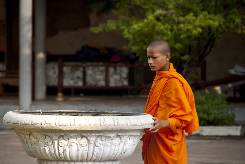 Buddhist monk looking somberly down at a fountain