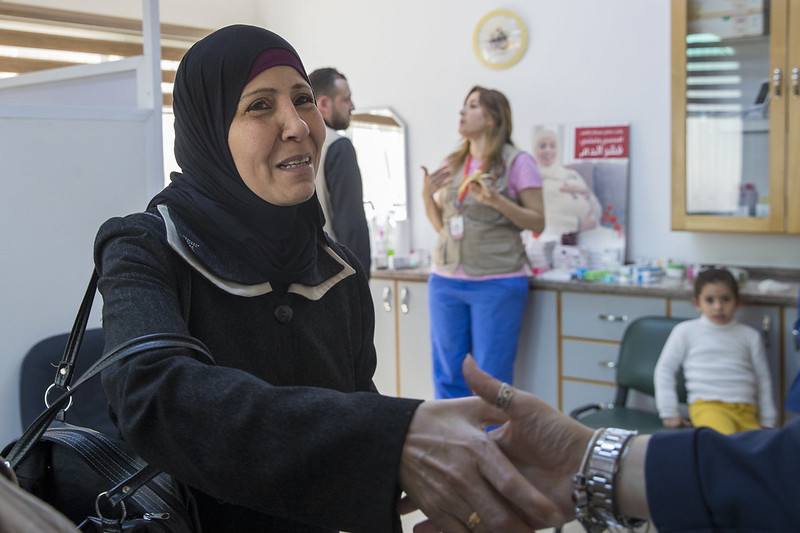 Refugee woman shaking doctor's hand