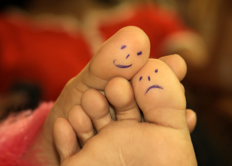 Photo of feet with happy and sad faces drawn on big toes.