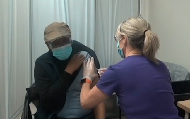 Interpreter Bogale receiving the COVID-19 vaccine