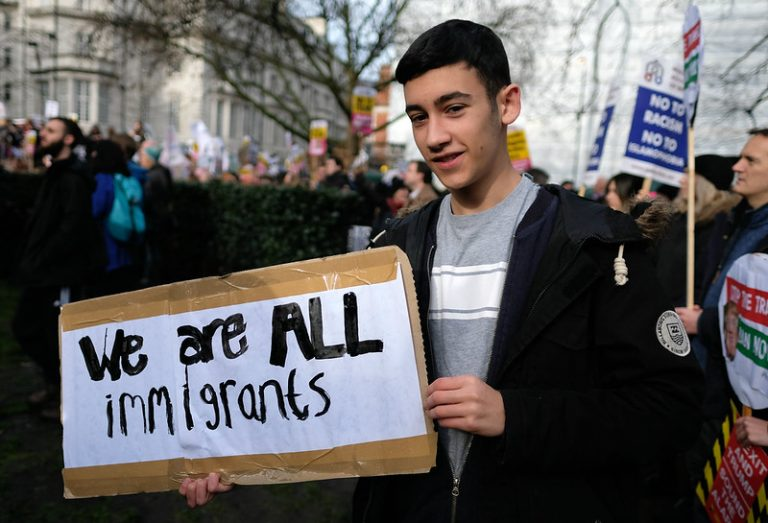 Young man holding sign that says We Are All Immigrants