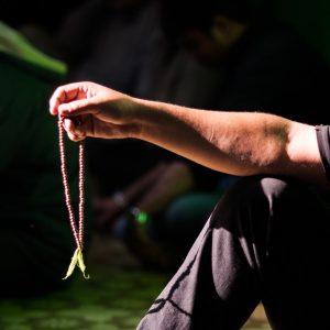 Image of man holding beads.